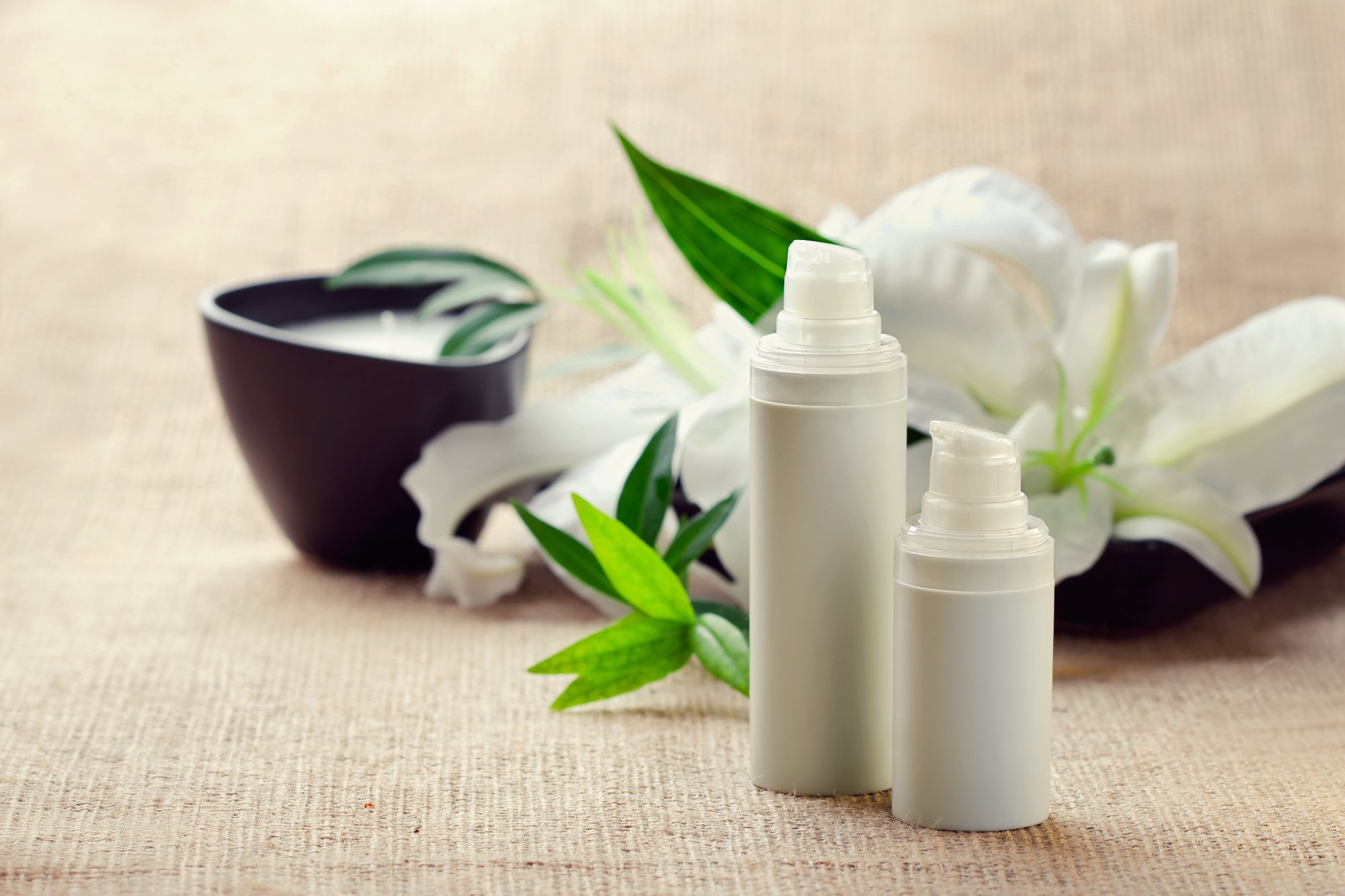 Face/body care concept: bottles of creams/lotions/serums with white lily flowers, closeup shot