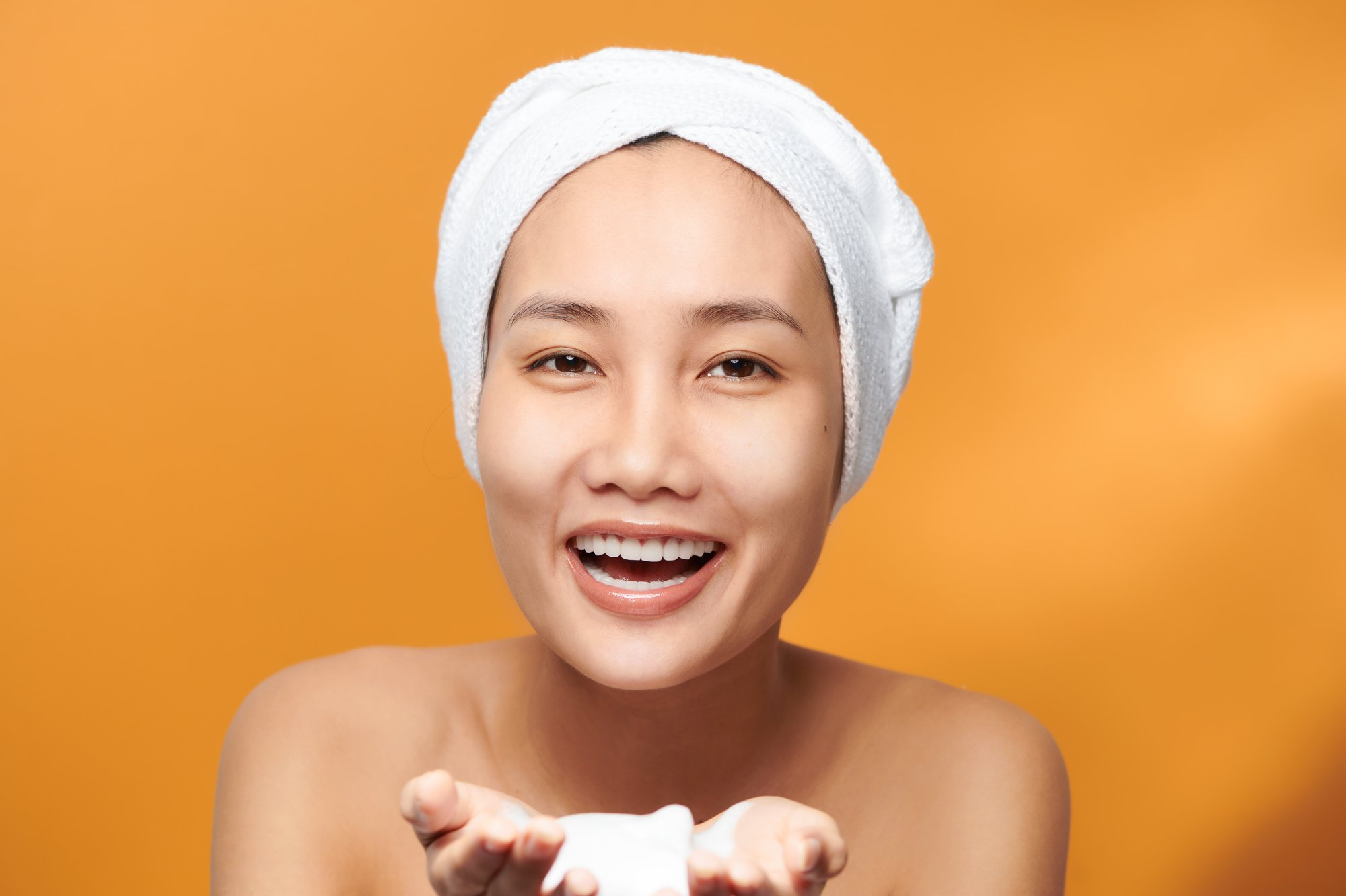 Cheerful Asian female holding foaming cleanser, has clean fresh healthy skin