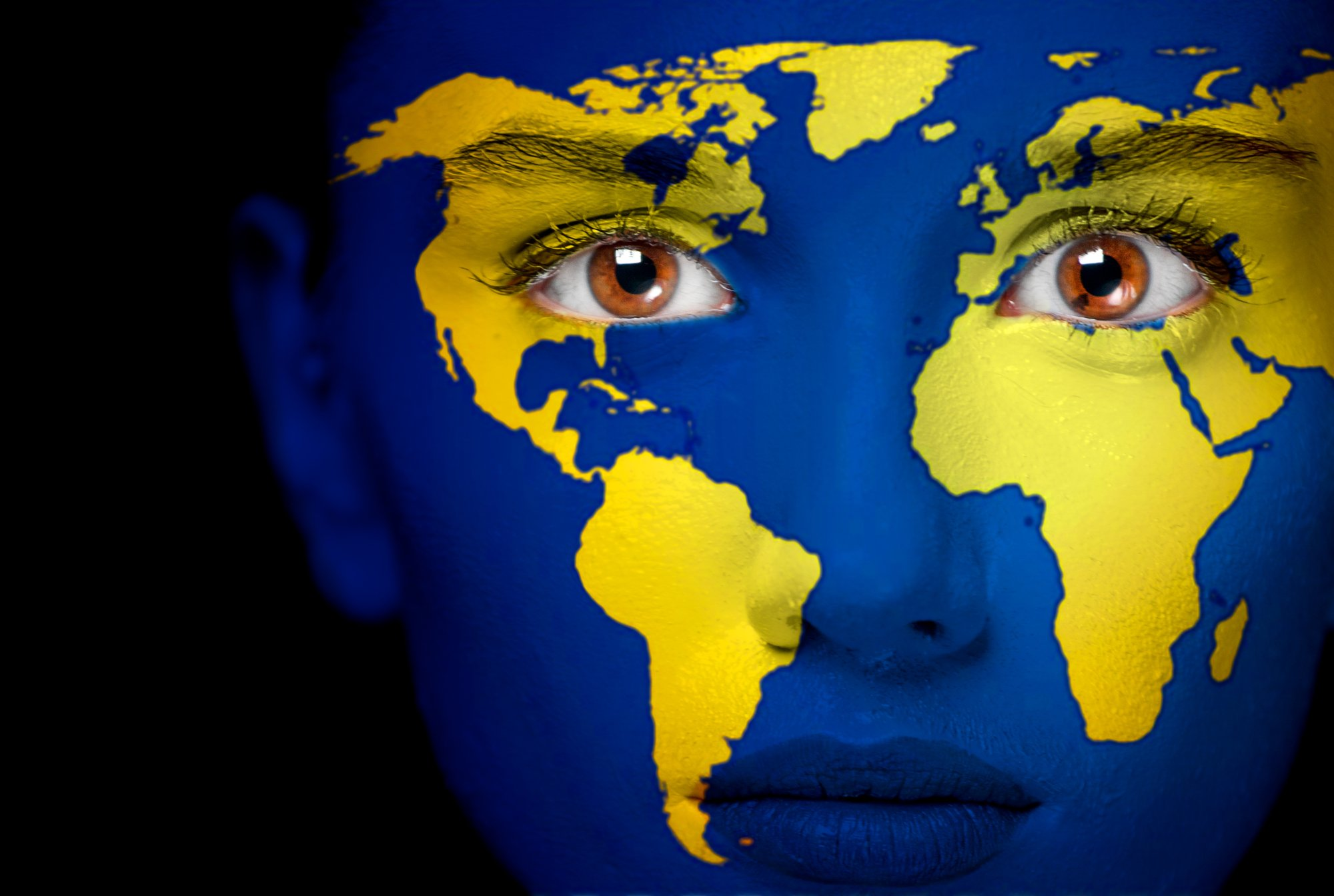 Portrait of a woman with the map of the world painted on her face.