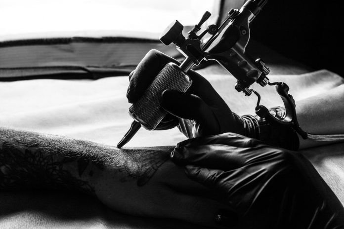 tattooist-makes-tattoo-on-clients-arm-in-bw